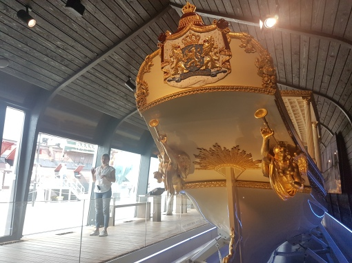 inside a room that holds an old small royalty boat for serious pomp and pageantry.